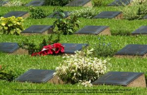 A Wreath-Of-Poppies rests against the grave marker of Lance Corporal John Alan Gilbert, Age 25, Queens Own Royal West Kent Regiment - Plot 12 Row B Grave 11, Taukkyan War Cemetery, Myanmar-Burma