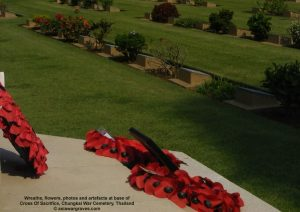 Wreaths, flowers, photos and artefacts at base of Cross Of Sacrifice, Chungkai War Cemetery, Thailand.